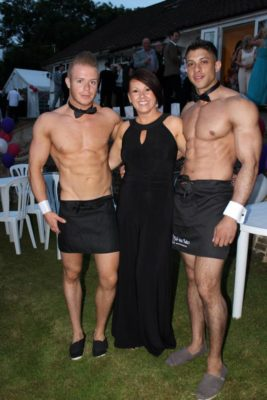 2 butlers and guest posing outside in the garden for picture