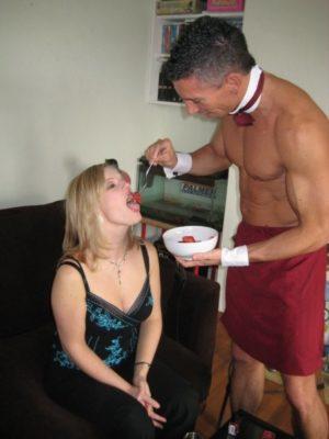 butler feeding girl with strawberry